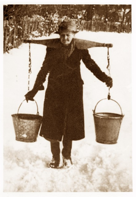 Lady carrying water home from the village pump in Stagsden aound 1918/9.  Many village houses did not have running water at this time.