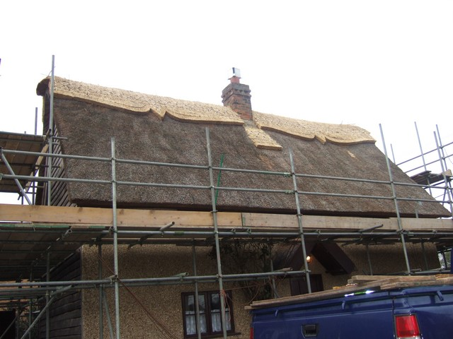 Scaffholding is put up so the men are able to work at the hight of the roof to thatch it.