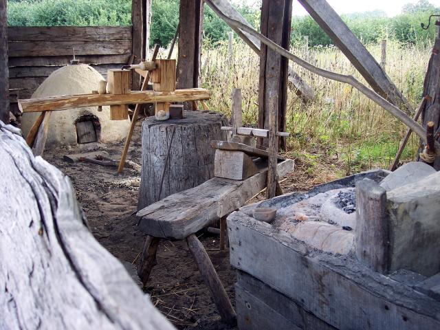 The pole-lathe was used to make wooden cups and bowls and tool handles.  People used their feet to turn the wood whilst it was shaped with a cutting tool held in the hand. The oven would be used to fire pots. Picture taken at West Stow, Suffolk 2006.