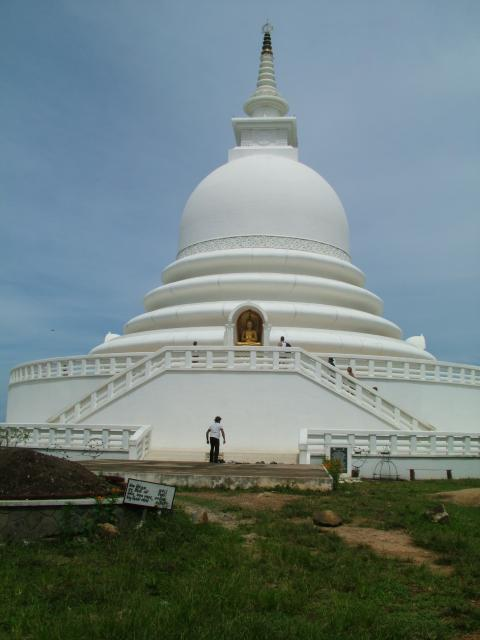 A grand white and gold Buddhist temple built on a cliff overlooking the sea on the coast in Southern in Sri-Lanka.