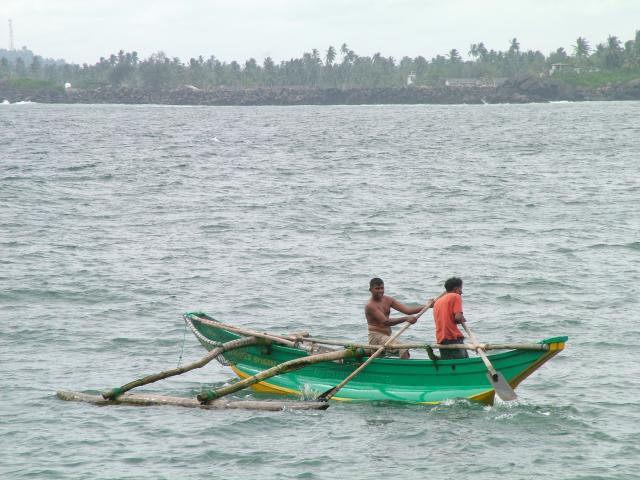 Local fishermen use a green boat to fish off the shores of Galle in Sri Lanka
