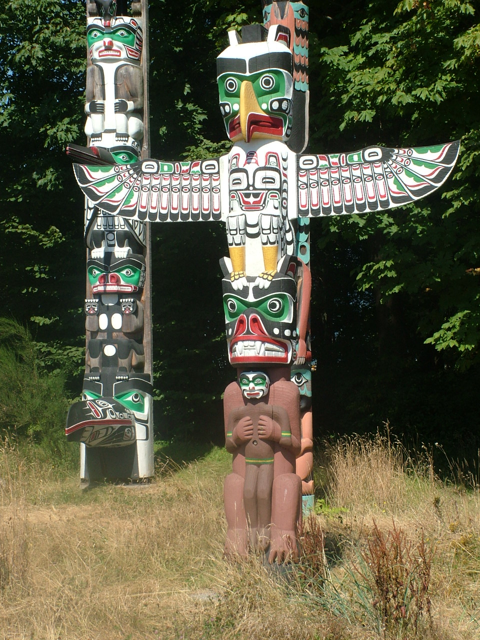 Totems in Stanley Park, Vancouver, Canada. The  four poles, all from the Alert Bay region on Vancouver Island, were purchased by the Park Board in conjunction with the Art, Historical and Scientific Society. Totem pole numbers increased as the City prepared for its Golden Jubilee Celebration in 1936...
