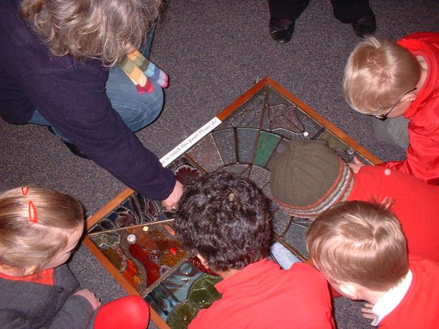 Children are given the opportunity to touch pieces of stained glass to see how they feel.