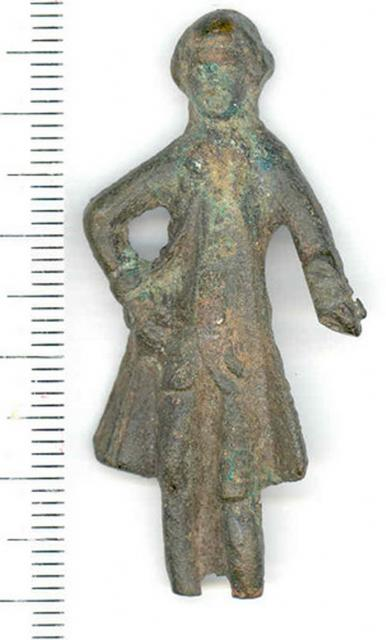 A post medieval copper alloy male doll found in Quidenham. The doll is wearing a long coat. � Norfolk Museums & Archaeology Service.