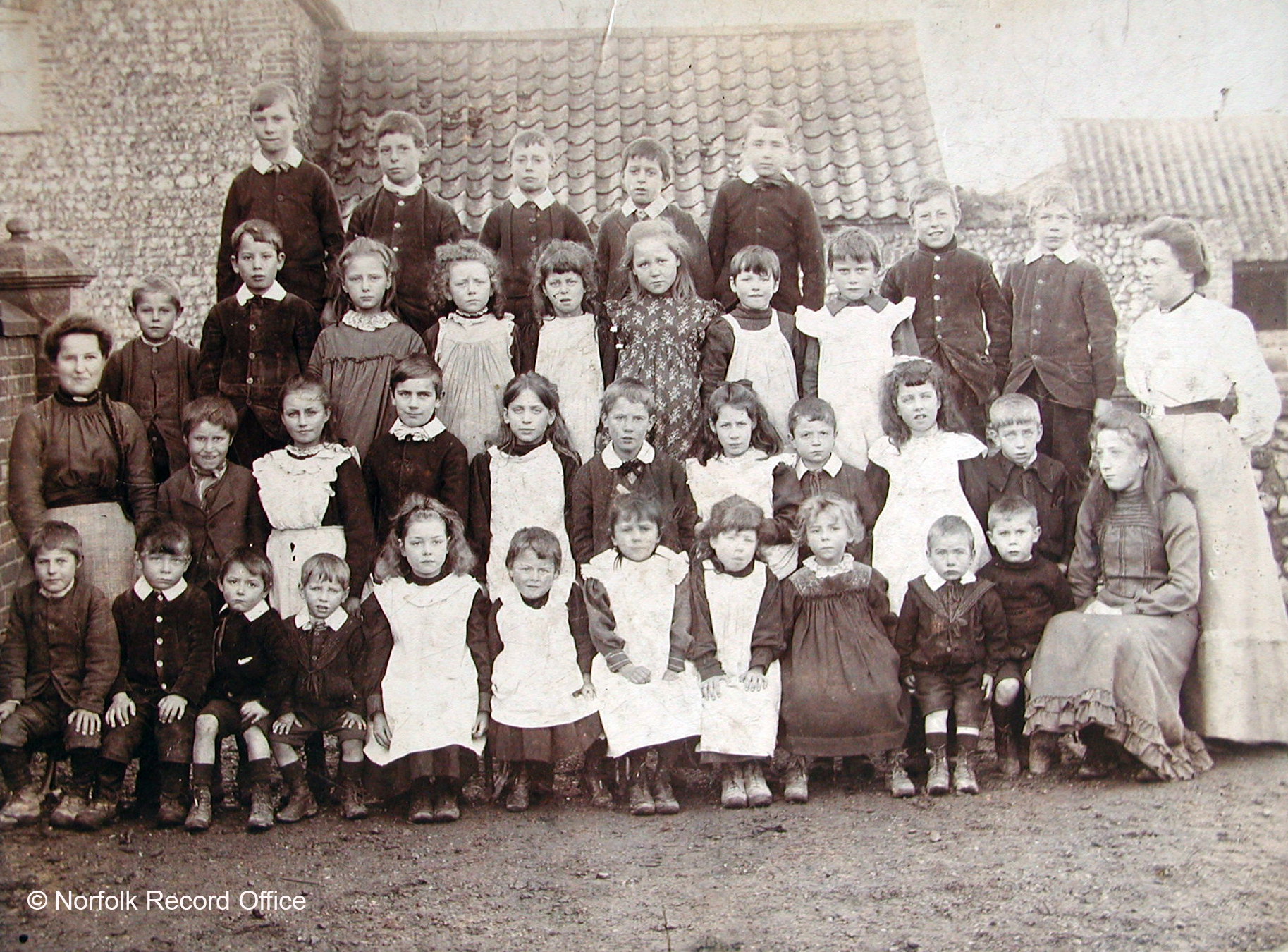 This photograph shows both boys and girls. Judging from the wide age range this is probably the whole school. The monitress on the left was May Twiddy, the teacher on the right was Miss Martha Burton. Children included in the photograph are front row: 1. George Barnes, 6. Evelyn Massingham, 7. Ethel...