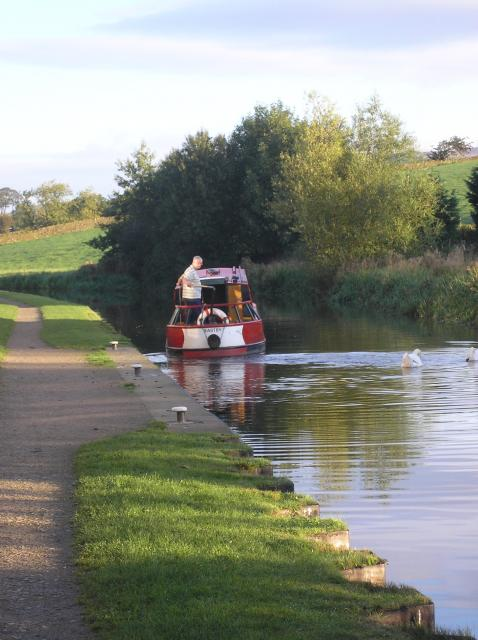 Canal barge moving off from the towpath after passing through the swing bridge on the Leeds-Liverpool canal