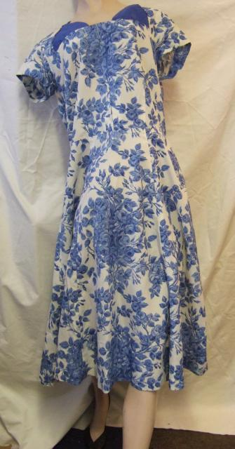 Woman's synthetic dress with printed design of blue roses c.1955=1960. Square necked, short sleeved, loose fitting bodice with box pleating and flared skirt reaching to just below knee.