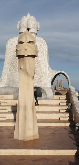 The figurines in this picture are chimneys on top of the Casa Mila building in Barcelona. In the background you can see the Cathedral - La Sagrada Familia, also designed by Gaudi.