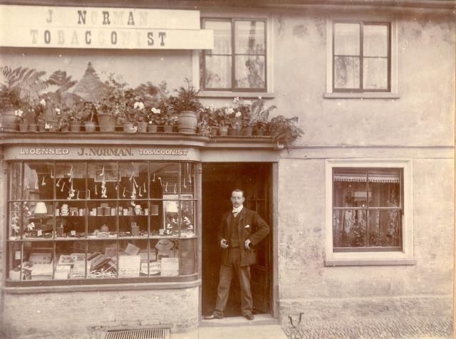 This was a tobacconist's shop owned by Mr Norman.  It has now been incorporated into the newsagent's shop on the corner.  Mr Norman is seen standing in the doorway.  He was the maternal grandfather of John Hubbard of Worlington whose wife Doreen was a teacher in the area for many years and at one ti...