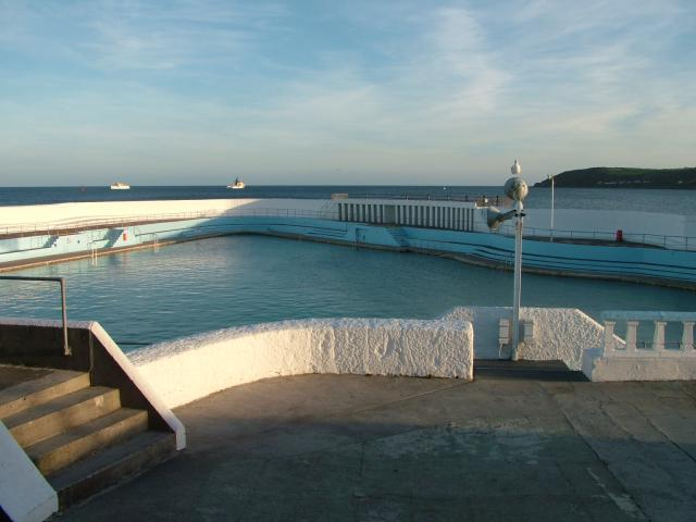 The Jubilee Pool at Penzance was opened in 1935 right on the shore line and therefore had to be able to deal with the ferocity of the Cornish seas. The pool is triangular in shape and is the largest open-air sea-water tidal swimming pool still in use in the UK.