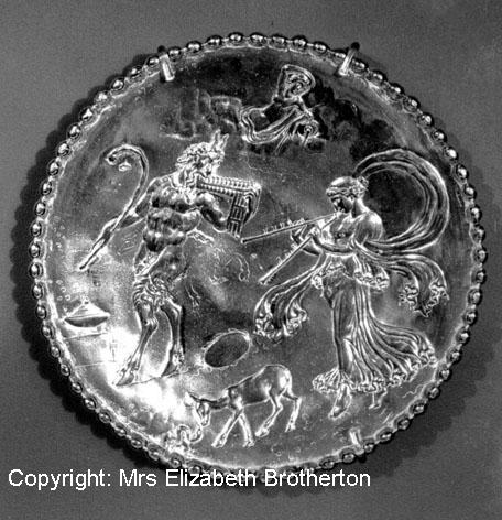 One of a matching pair of small platters.  Pan can be seen holding a shepherd's crook and playing a syrinx whilst a Maenad plays a double flute.  At the top is a reclining water nymph whilst lower down a fawn or doe investigates a snake.