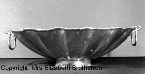 This large, shallow, fluted bowl with two swing handles was probably intended to hold water for washing hands at table.  The bowl has alternate fluted and flat radial panels, the leaf pattern on the flat panels closely resembling that on three of the spoons in the hoard.  The central circular panel ...