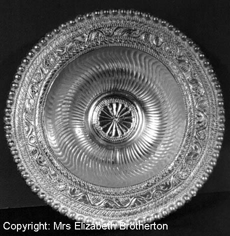 This is one of an almost identical pair and is of similar form to the four larger flanged bowls.  The rim is richly decorated with leaves, flowers, grapes, birds and rabbits within a vine scroll.  The inside is gently fluted and has a central rosette motif of sixteen petals.