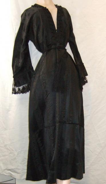 Woman's dress in alternate broad stripes of black satin and moire silk c.1910=1915. Wide V neck open to waist; long Magyar sleeves, tight at shoulder but wide at cuff. Round waist at natural level. Ankle length skirt