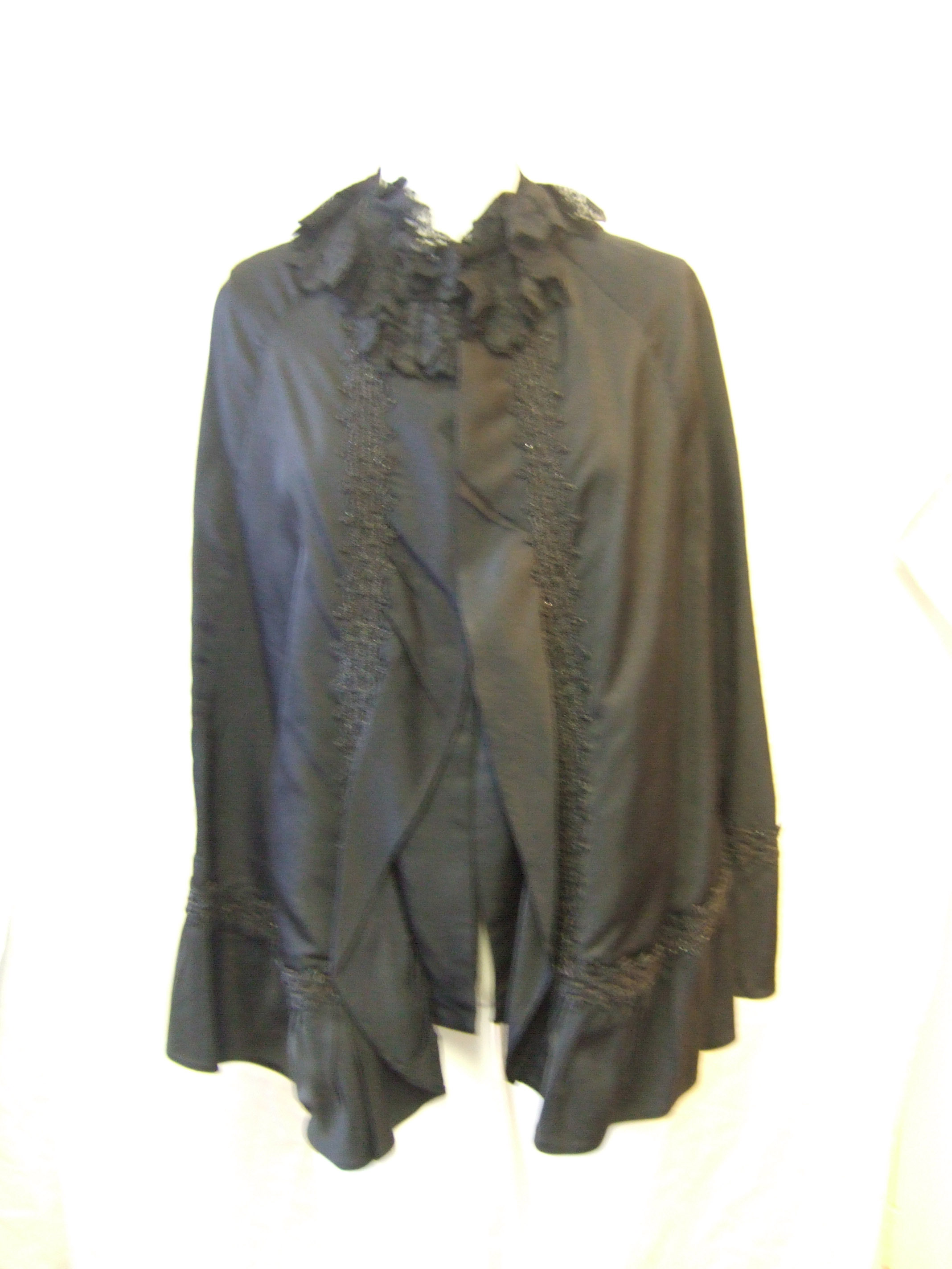 Woman's cape in black silk satin c.1900-1920. Made of 8 panels, darted to give slight shaping at the shoulder. Small stand collar trimmed with black machine lace.