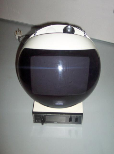This television was designed in 1970 to look like a space helmet, just after the first moon landing in 1969. This model was made in 1974 and aimed at the Youth market in the UK and Europe. Made from plastic acrylic, glass and metal it was durable and came in other bright colours such as orange. It i...