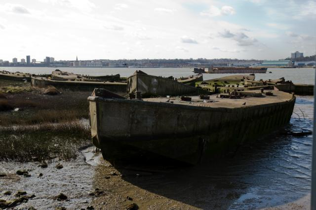 A whole platoon of concrete barges at Cold Harbour Lane, Rainham on the north bank of the Thames. During the Second World War, steel was in short supply. Governments in the UK and the US ordered the construction of barges made of reinforced concrete. The barges now abandoned on the Thames mud at Rai...