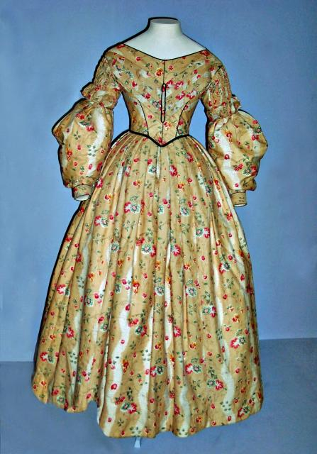 Soft colour and floral prints were popular int he early Victorian period. Here pink red and white flowers harmonise with the soft brown printed cotton and green silk and satin piping. The dress is lined with linen and cotton. The sleeves loose at the bottom emphasise the slope of the shoulders and t...