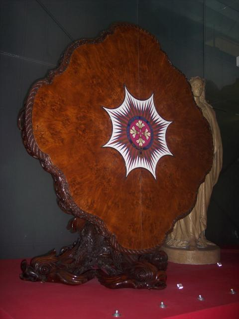 This large carved table includes national emblems and naturalistic motifs. The central motif is inscribed 'Hail Star of Brunswick. The table is in walnut with carved inlay of pollard oak and a porcelain plaque. It was designed and manufactured in Bath by the factory of Henry Eyles and the plaque mad...