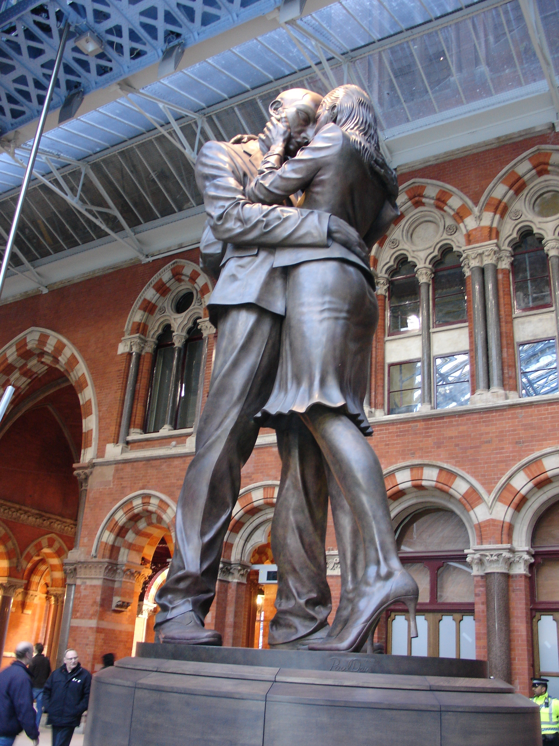 This sculpture stands under the central clock at St Pancras station in London.  The bronze sculpture is 9m high and was designed by Paul Day.