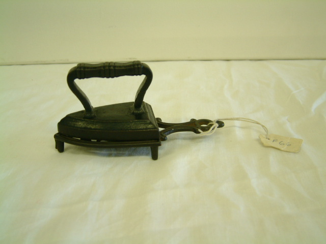 Toy iron made of metal. Approximately 5cm long. Stands on a metal base.