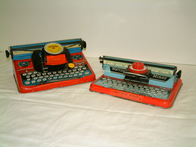 Metal toy typewriters with central turning dial with letters and numerals to select. In front of dial is a bar to press down when letter or number has been selected. Turning wheels at ends of bar for feeding in paper.