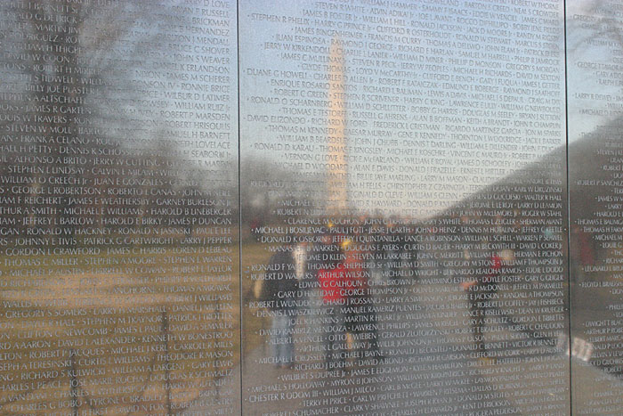 This image shows the Washington Memorial reflected in the highly polished stone wall that carries the names of those who died in the conflict.