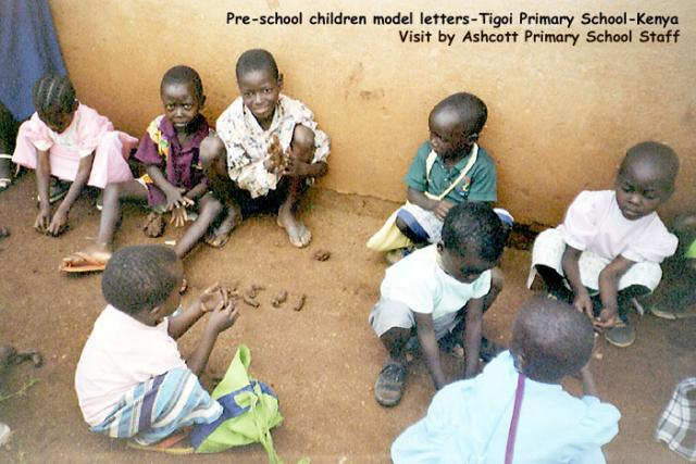 Pre-school children model letters in clay dug from the ground, Tigoi Primary School, Kenya