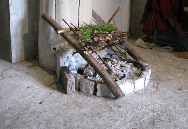 Neolithic open cooking fire, with a wooden griddle placed at a slant across it, on which to bake bread, cakes, fish etc.