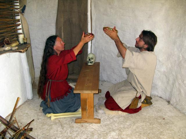 Neolithic couple performing a domestic religious ceremony together over the bones of an ancestor.