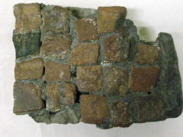 This is part of a tessellated pavement,often found in Roman villas. Each square is called a tesserae. This form of decoration was called a mosaic.