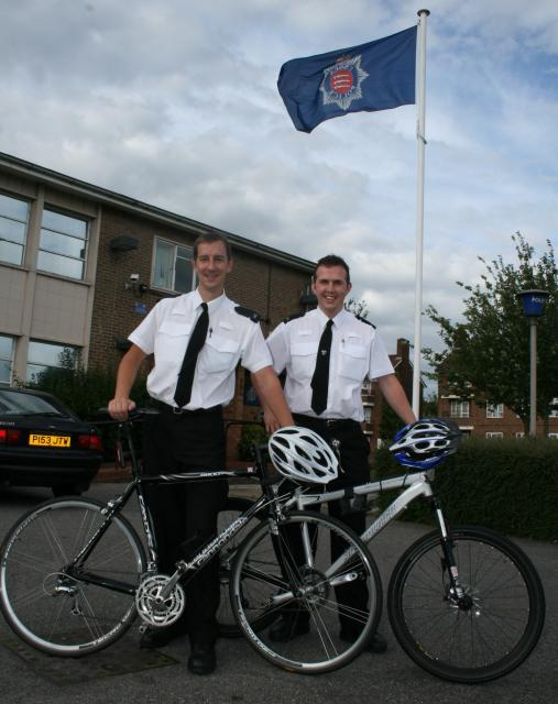 Two police officers with push bikes and helmets outside a police station.