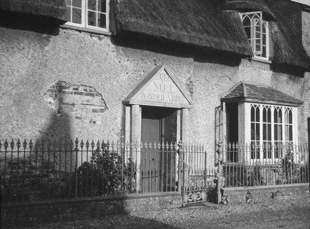 "This photograph is from a lantern slide. It shows a thatched house in Fen Drayton, Cambridgeshire. There is an inscription in Dutch above the front door ""Niet Zonder Arbyt"" - ""Nothing achieved without labour"" 1713. Villages near Huntindon and Ely such as Fen Stanton and Fen Drayt..."