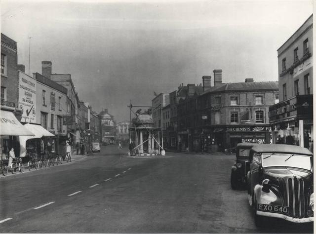 The Conduit in Chelmsford's High Street marked where water from a medieval well sprang up. It was removed in April 1940 as the structure was deemed to be a danger and an obstacle to traffic at the junction where it stood. Traffic lights were installed instead. The Conduit was re-erected in Tower Gar...