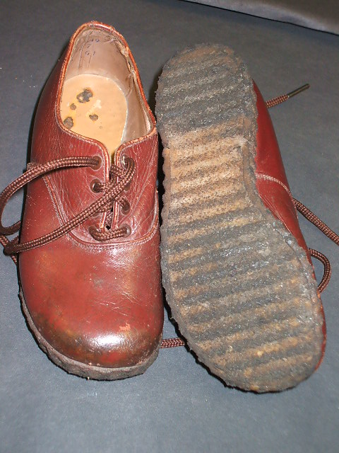 This is a pair of children's shoes from World War 2. They are made of a tough leather and have been well looked after as clothing was rationed during the war.