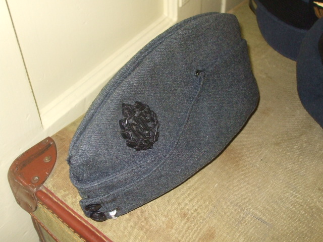 This hat was used by RAF personnel in the second World War. It was known as the cheese cutter because of it's wedge shape. It could also be carried on a soldiers' shoulder flattened under his epaulette.