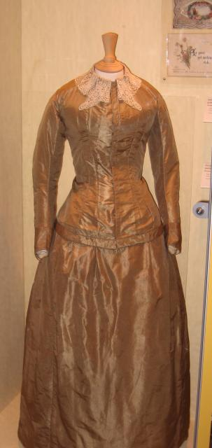 This dress is a ninteenth century Victorian wedding dress. It has a silk and lace bodice, with a skirt and small bustle. Note how the colour of the dress differs from the now traditional white as well as the tiny waist