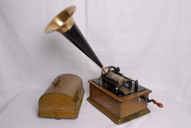 When this phonograph was first made, people used it to record their own voice, it then became one of the first commercially produced machines, when it was used to play music. It worked by vibrating the stylus up and down whilst moving across the wax cylinder (Hill & Dale method).
