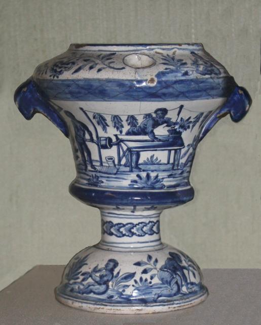 This vase shows enslaved people making a rope twist of tobacco on a plantation. In the 18th century the price of tobacco had decreased and all ranks of society, even farm labourers could afford to smoke it. Bristol was one port that was an important centre for tobacco processing. With thanks to 'The...