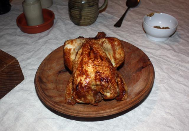 A cold, cooked chicken resting on a wooden platter ready to be sliced and layered into the salad. The chicken bones and scraps would be boiled afterwards to make stock for other dishes.