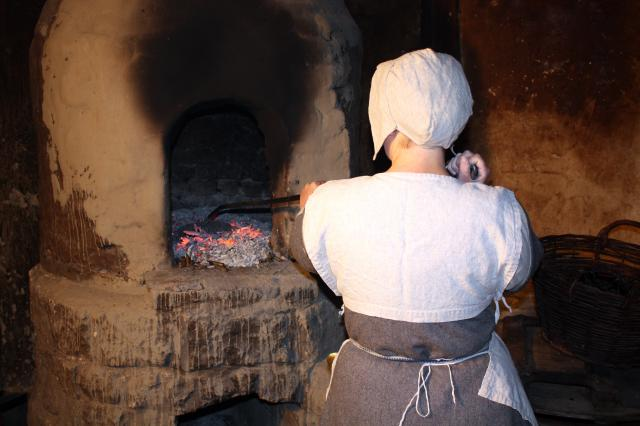 Tudor cook removing bread from oven