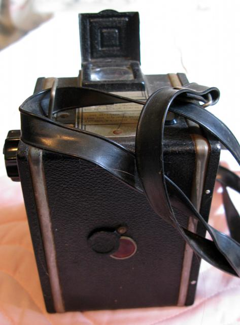 BoxCamera made in England. Uses 620 or 120. Black covering. Meniscuses lens, single speed shutter. Built in colour filter.