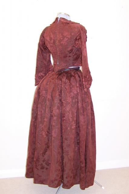 Skirt, long and top.  Wine coloured, damask material. Skirt taken in at the waist. Top has book lace tied back, rucked (self material ribbon) front and cuffs with hook fasteners. Extra piece to infill waist opening