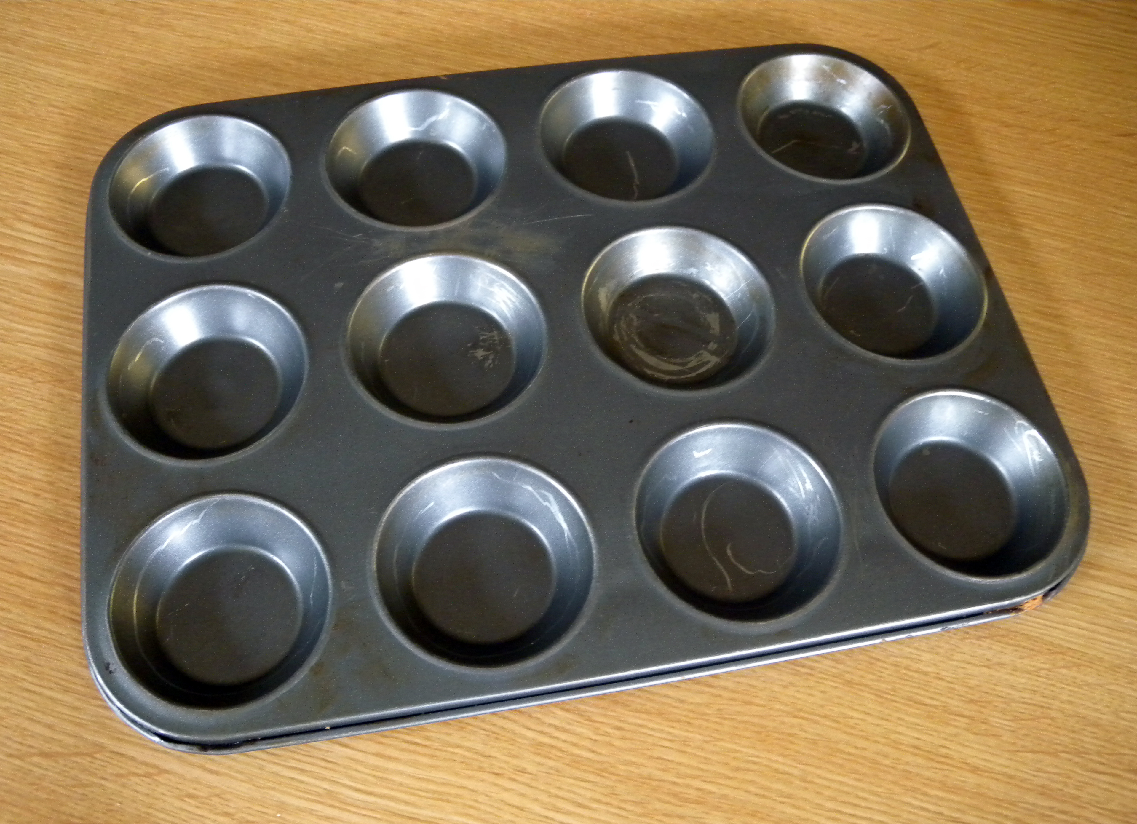 A baking tray or tin with six, nine of twelve shallow round depressions for putting in batter or dough to make buns, pastry or cakes.