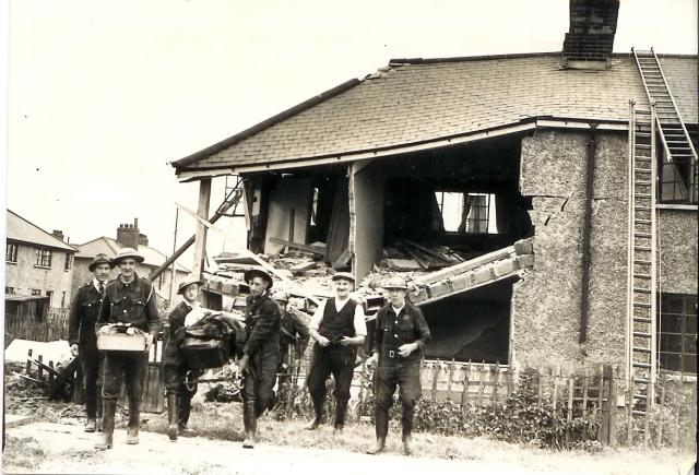 House in Feenan Highway, Tilbury Town, hit by a high explosive bomb. Civil defence workers helped to rescue furniture and belongings.