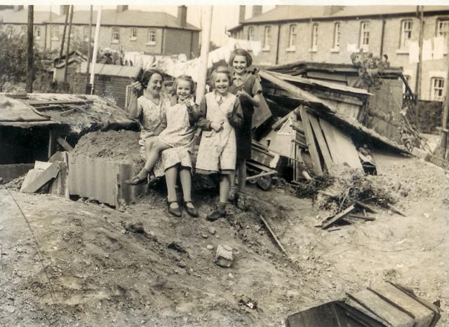 A lucky family survey the damage to their housing estate at Purfleet and their  survival inside their war shelter is amazing.