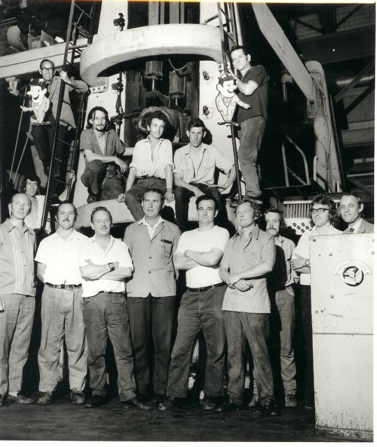 Workers stand by one of the huge mechanical mills making cardboard and paper rpoducts in the 1960's.