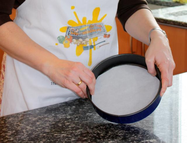 Lining a cake tin is putting greaseproof paper, or similar, around the inside of a tin before adding the uncooked mixture, so that when baked, the cake does not stick and can be removed from the tin more easily.