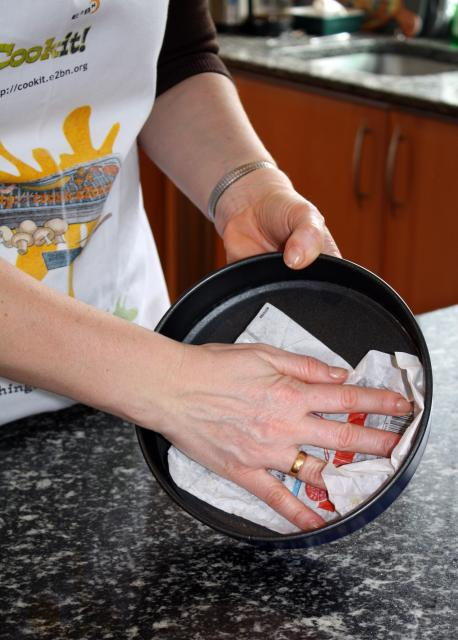 Greasing is brushing a baking tray or cake tin with oil, or rubbing it with butter or lard, to stop food from sticking.