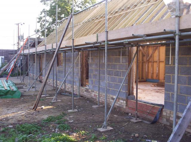 Scaffolding has been erected after new block walls have been built around the timber frame.